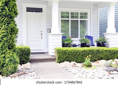 Schönes, nagelneues weißes Haus in einem kanadischen Viertel. Die Eingangstür ist mit einer hübschen Veranda und einem Felsgarten versehen.