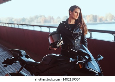 Beautiful brave woman is leaning on her motobike in tunnel. She is holding helmet.