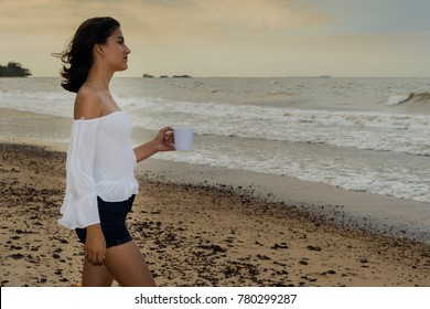 Beautiful brazilian girl having a cup of coffee tea having a cup of coffee tea on a beach at sunset, looking away serious pensive. Happiness in nature concept. Space for text