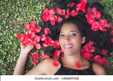 beautiful brazilian woman, 37 years old, brunette, with beautiful smile lying on the lawn surrounded by red rose petals