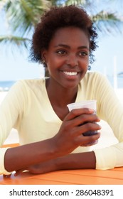 Beautiful brazilian woman at beach drinking soda