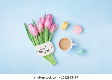 Beautiful breakfast on Mothers or Womans day. Coffee cup with pink tulip flowers, macaroon and note good morning on blue table top view.