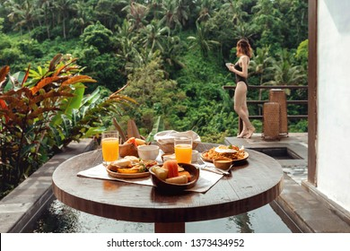 Beautiful breakfast on a wooden table against the background of the pool and a young beautiful woman in a bathing suit with a cup of coffee in hand. Sumptuous breakfast in the tropical jungle, Ubud,