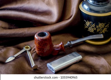 beautiful briar setter pipe on silk background, with a birdseye bowl, czech tool, silver flint lighter and elegant humidor