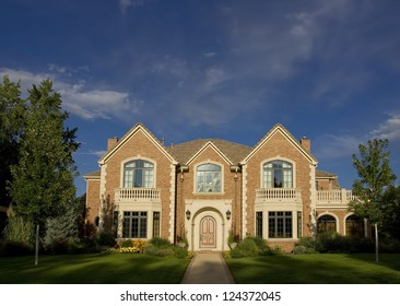 Beautiful brick home with blue sky. Wide Shot.