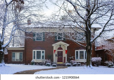 Beautiful brick house with bay windows with Christmas tree showing through and decorated pillars and sled on porch in snow framed by winter trees