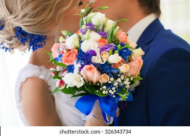 beautiful bridal bouquet close-up on a background of kissing newlyweds