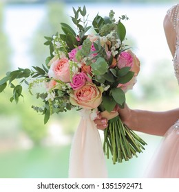 Beautiful bridal bouquet in hands of the bride. Wedding bouquet of peach roses ,  single-head pink rose aqua, eucalyptus, ruscus, gypsophila