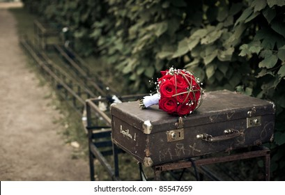 Beautiful bridal bouquet of red roses is lying on the vintage shabby suitcase at ferrous stand in the park