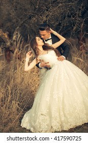 Beautiful bridal couple of young man embracing pretty woman in sunlight in field