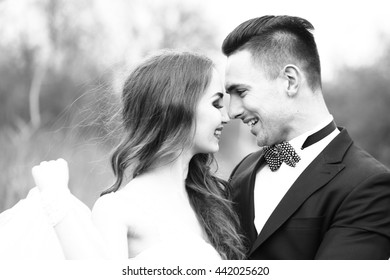 Beautiful bridal couple of young man embracing happy pretty woman outdoor, black and white