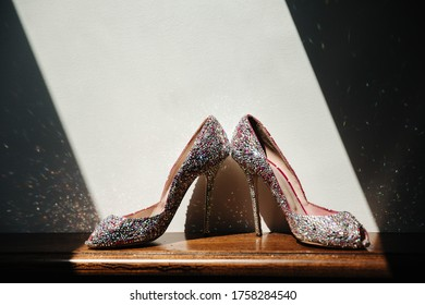 Beautiful bridal high and blossom golden stiletto heel shoes. Luxury designer wedding shoes on the table with beautiful light captured