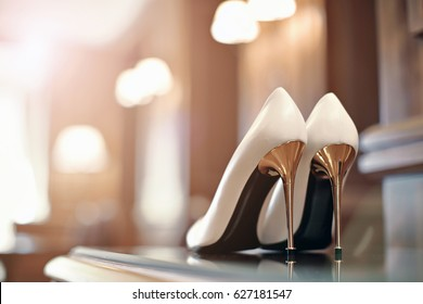 Beautiful bridal high and thin golden stiletto heel shoes. Luxury designer wedding shoes on the table.