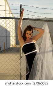 Beautiful bride against a metal fence