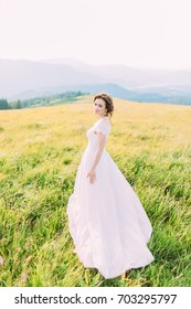 beautiful bride among grasses and flowers.