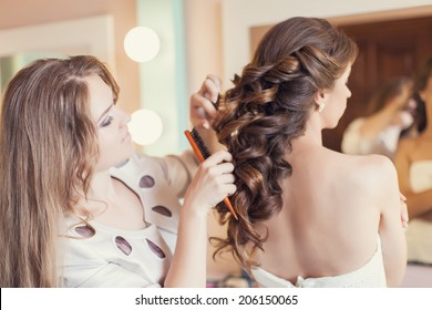 Beautiful bride applying wedding make-up by professional make-up artist on the wedding day