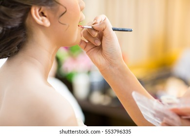 Beautiful bride applying wedding make-up by professional make-up artist on the wedding day.blur image of people at haircut shop.Women's haircut. hairdresser, beauty salon.