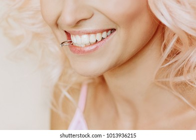 beautiful bride blonde holding a wedding ring in her teeth and smiling