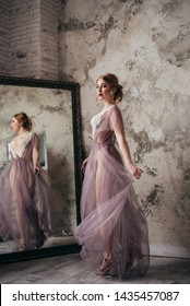 A beautiful bride in a boudoir dress is spinning near the mirror.