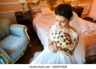 beautiful bride with bouquet of flower posing in luxury room