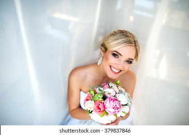 A beautiful bride with a bouquet in hands laughs and poses. Bride smiling near a window
