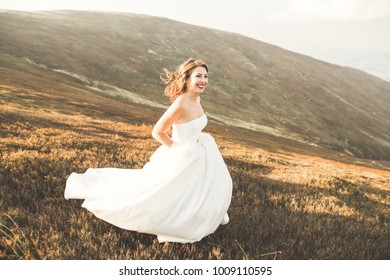 Beautiful bride with a bouquet on mountain background at sunset