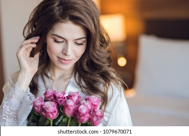 Beautiful bride with a bouquet of roses indoors