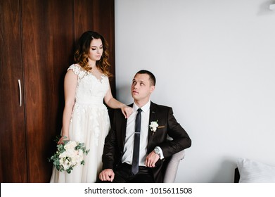 Beautiful bride with a bouquet of wedding flowers and the groom with a boutonniere on a suit. Wedding ceremony. Man looks on a woman.