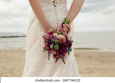 Beautiful bride with bridal bouquet at the beach