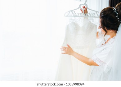 beautiful bride with bridal veil touches the wedding dress on the background of a window with a tulle and a curtains. beautiful hairdo