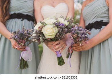 Beautiful bride and bridesmaids closeup. Caucasian women holding bouquets of purple flowers in their hands. Happiness, friendship concept.