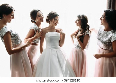Beautiful bride & bridesmaids posing near window, wedding preparation