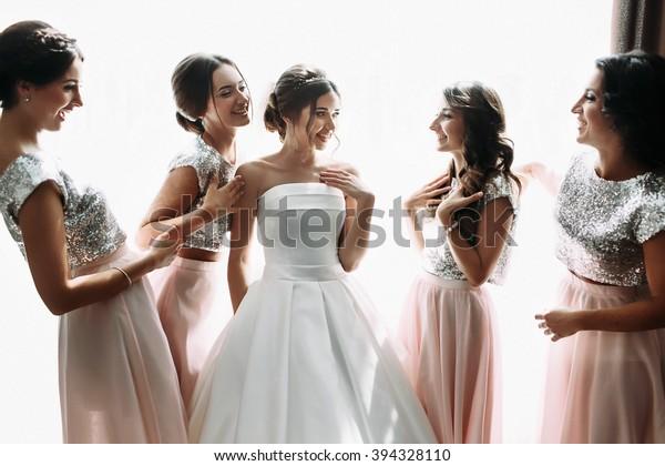 Beautiful bride & bridesmaids posing near window, wedding preparation
