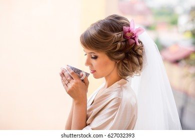 Beautiful bride with cup of coffee at wedding morning. Beauty bridal makeup and hairstyle with orchid flower.