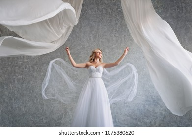 A beautiful bride with curly hair and a long veil in the studio with white flying curtains. A sweet bride depicts a bird. The flight of the bride. Wedding idea in the studio.