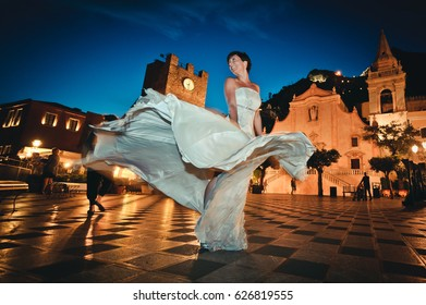 Beautiful bride dancing and celebrating her wedding in the charming scenario of an historical square in Taormina