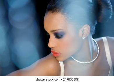 Beautiful bride with dark skin sitting around blue bokeh flares (bokeh originally shot like this).
