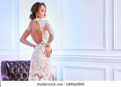 Beautiful bride in dress posing in the studio on a colored background. Shop wedding dresses, bridal makeup, chic hairstyle, storefront