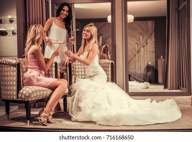 Beautiful bride in elegant wedding dress and her friends are drinking champagne, talking and smiling while sitting in modern wedding salon