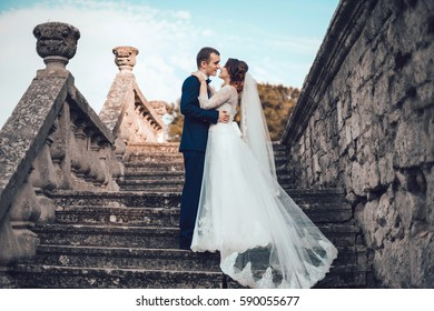 beautiful bride embraces fiance against the background of the old castle and blue sky. White veil fading away in air. Greece. a beautiful couple in love