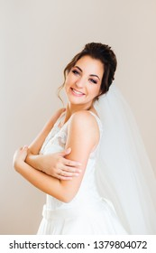 beautiful bride embraces herself and looks at the camera on the background of the wall. sincere bride's smile