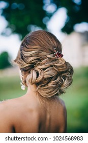 Beautiful bride with fashion wedding hairstyle outdoors. Closeup portrait of young gorgeous bride.