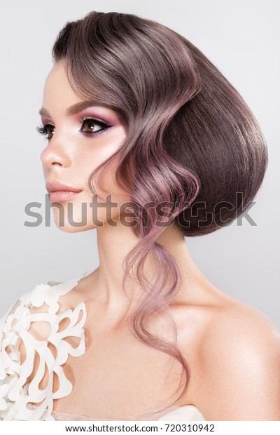Beautiful bride with fashion wedding hairstyle - on white background.Closeup portrait of young gorgeous bride. Wedding. Studio shot.