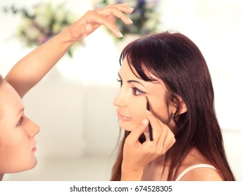 A beautiful bride gets cosmetics for centuries from a female make-up artist with a brush. Young woman with long brown hair in a beauty salon.