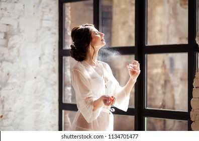beautiful bride girl holding perfume in her hands and applying it