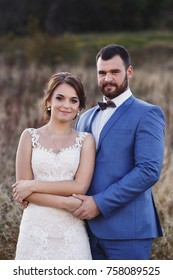 beautiful bride and groom in the dry grass, sun rays
