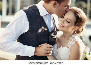 Beautiful bride and groom embracing and kissing on their wedding day outdoors