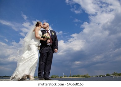 Beautiful bride and groom kissing on the background of clouds