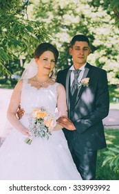 Beautiful bride and groom on the background of green foliage in summer sunny day