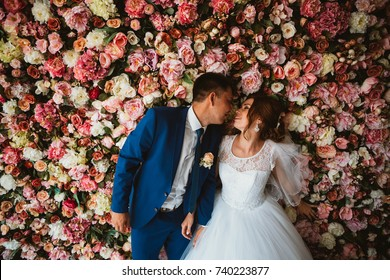 beautiful bride and groom on the background of a wall of flowers.